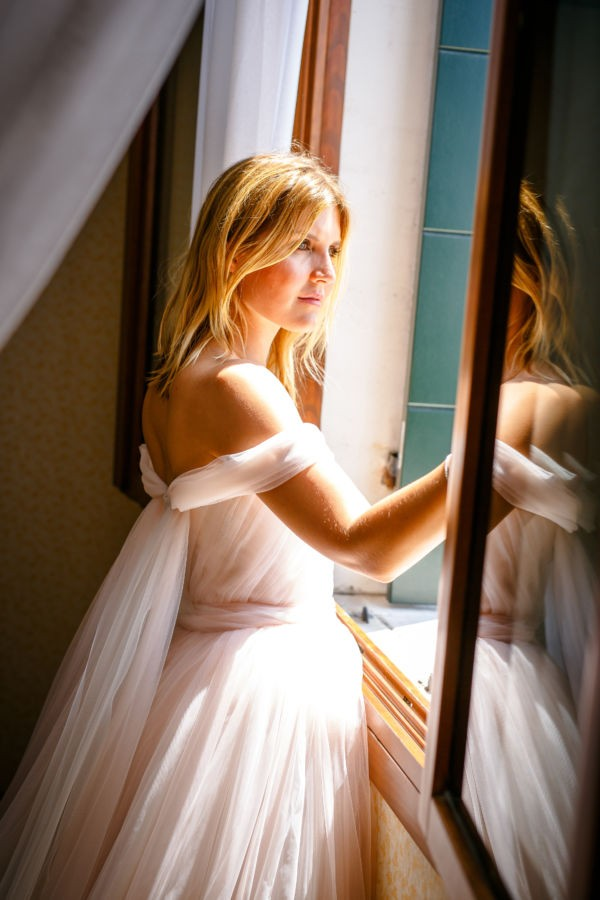 Die Braut steht am Fenster und sieht hinaus