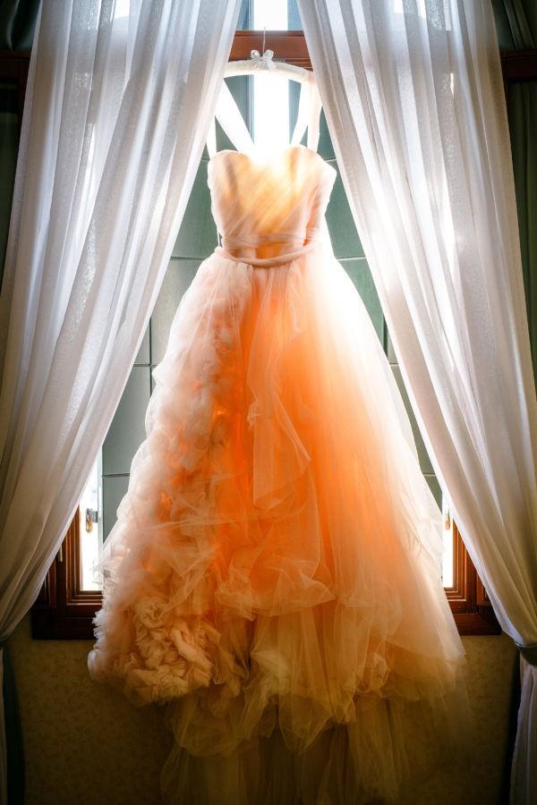 das Brautkleid hängt am Fensterrahmen und sie Sonne lässt die Farben miteinander spielen