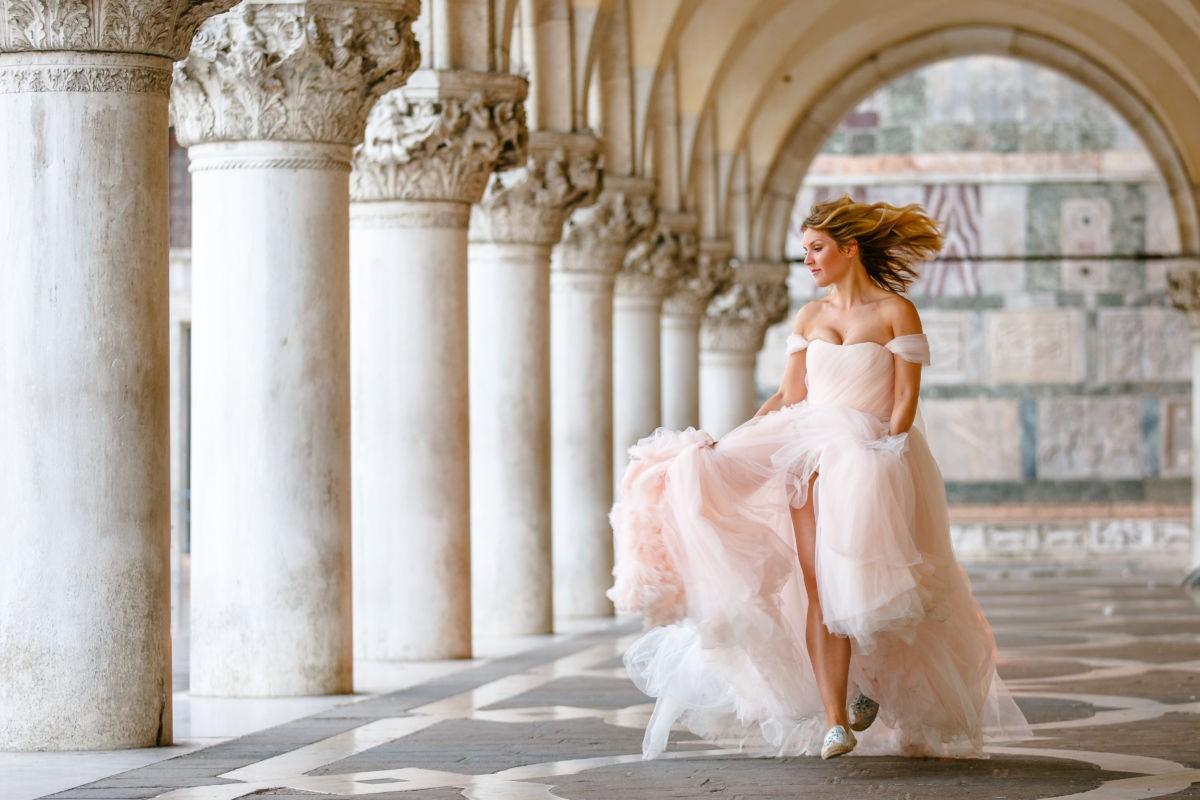 Die Braut läuft durch den Säulenpark und ihr Kleid schwingt wie eine Wolke um sie herum