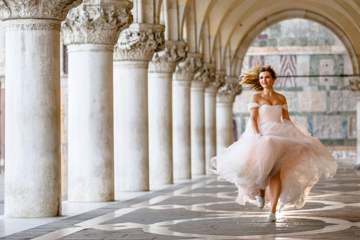 Braut läuft durch einen Säulenpark in Venedig. Sie sieht aus wie eine Prinzessin. Ihr Kleid schwingt wunderschön. Sie ist glücklich.