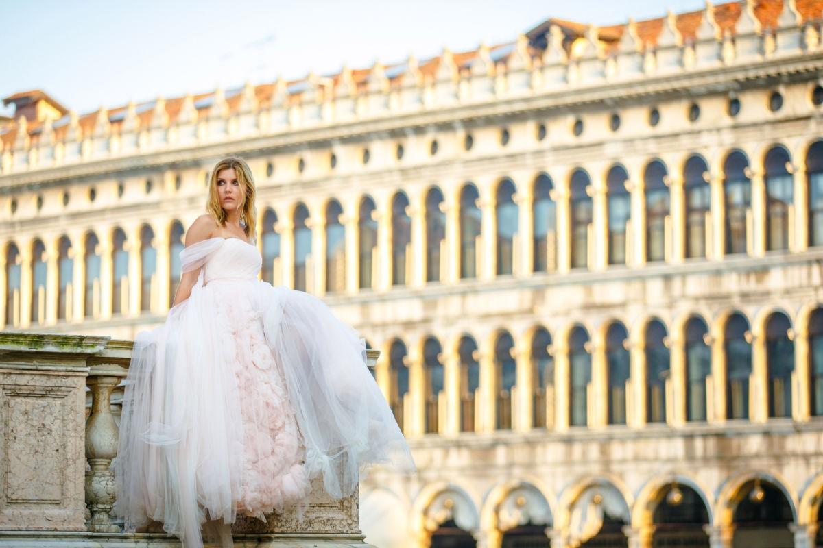 Die wunderschöne Braut sieht aus wie eine Prinzessin und sitzt gedankenversunken auf einer Säule auf dem Markusplatz in venedig. Im Hintergrund sieht man ein wunderschönes altes Gebäude.