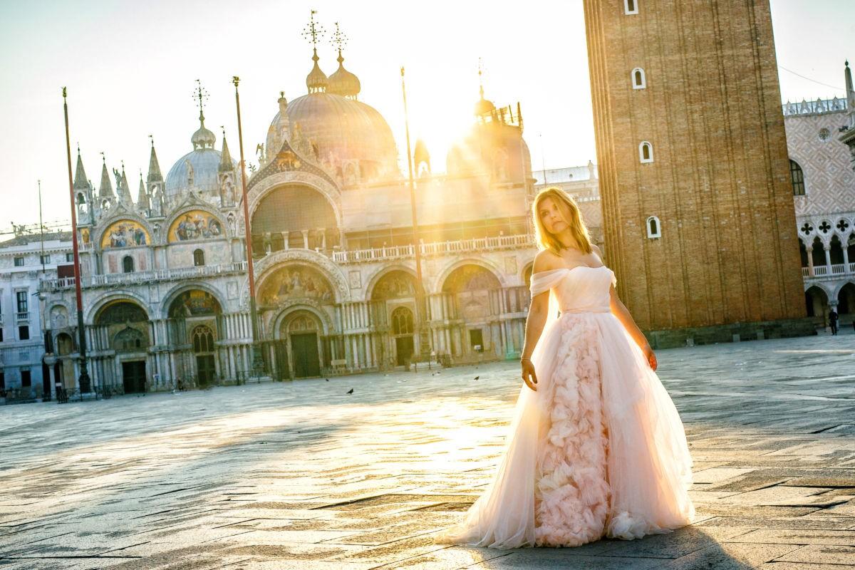 Eine Braut steht in ihrem Tüllkleid mitten auf dem Markusplatz. Im hintergrund geht zwischen den altehrwürdigen Gebäuden die Sonne auf und taucht das Geschehen in warmes Licht.