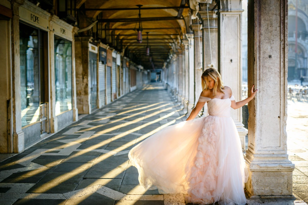 die Braut steht bei Sonnenaufgang in einem Säulenpark und spielt mit ihrem Kleid. Das Licht scheint durch die Säulen durch und lässt das geschehen in warmen Licht erstrahlen.