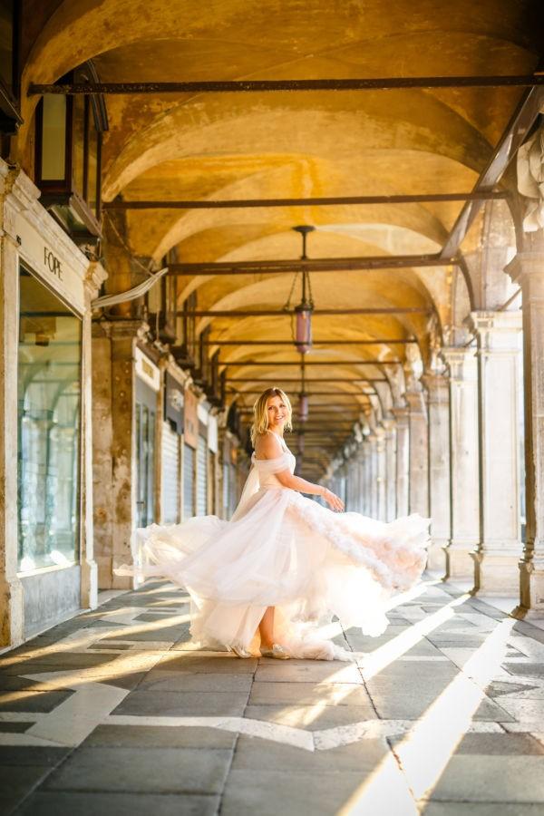 eine Braut im Prinzessinnenkleid dreht sich, während ihr Kleid verspielt um sie schwingt. Das alles vor der malerischen Kulisse Venedigs. Die Sonne strahlt mit hellem, warmen Licht.