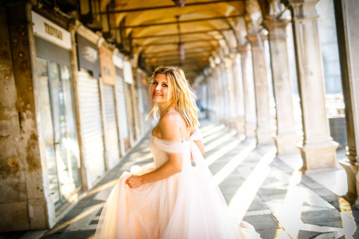 Die Braut schaut in die Kamera während sie davonrennt. Sie ist glücklich.