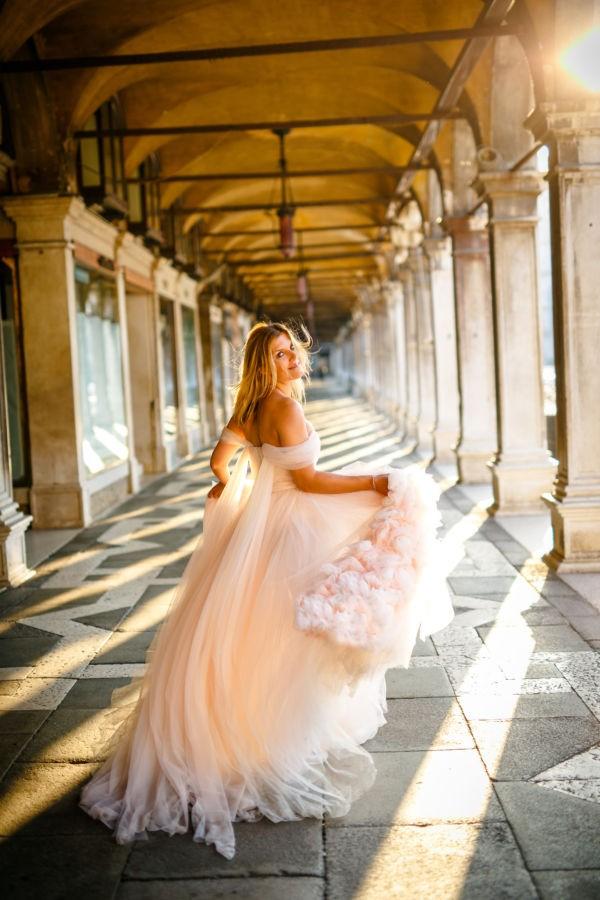 Die Braut schaut in die Kamera während sie davonrennt. Sie ist glücklich. ihr Kleid weht im Wind.