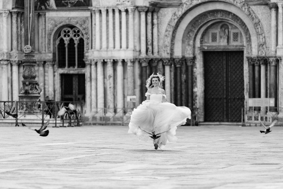 Eine Braut jagt auf dem Markusplatz in venedig Tauben. Ihr Kleid schwingt bei der Bewegung.