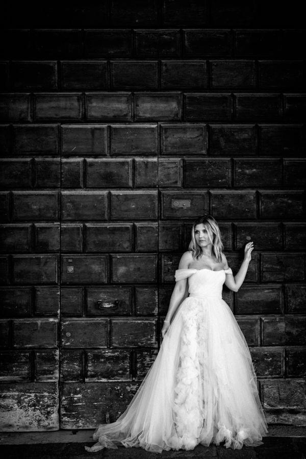 Eine schöne Frau steht in einem Brautkleid vor einer gigantischen alten Holztür. Das Bild ist schwarz weiß.