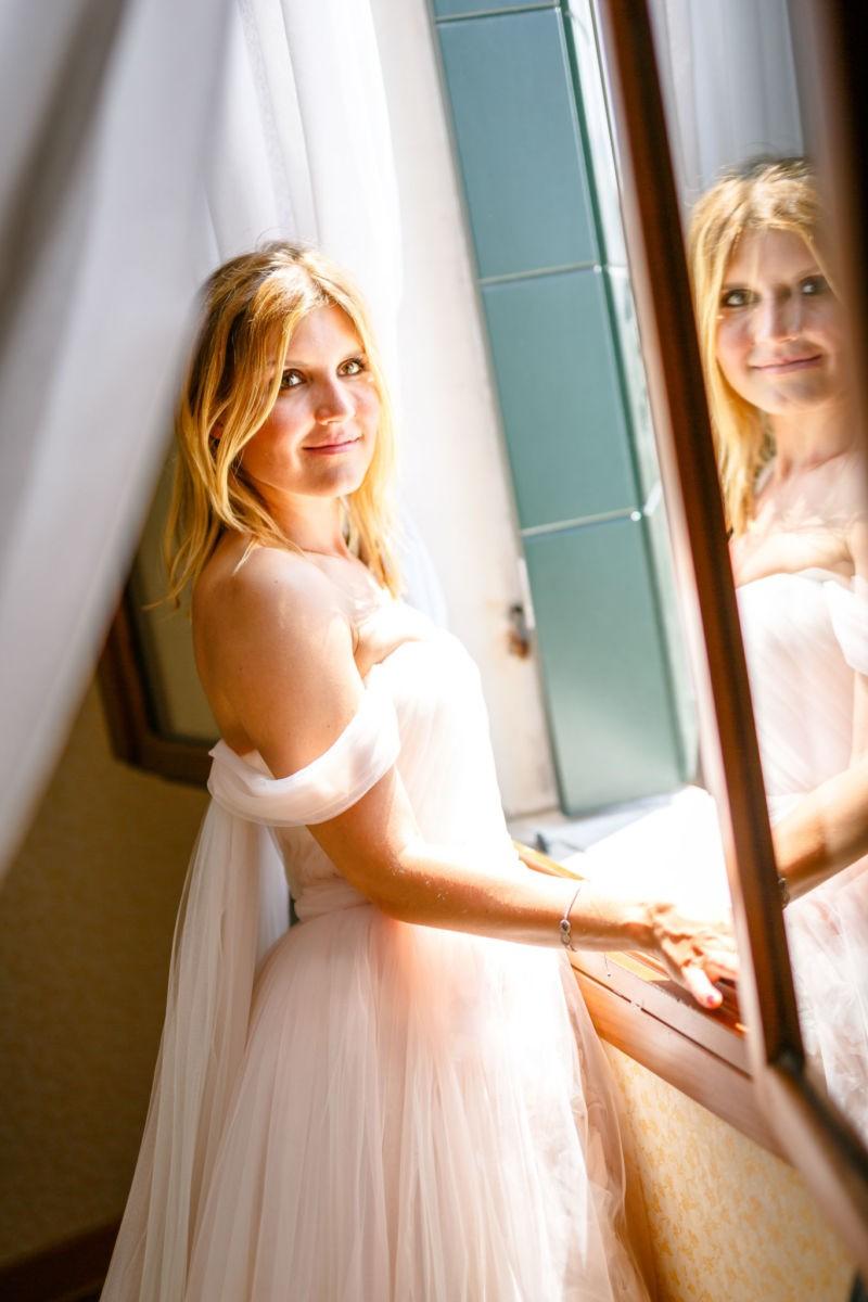 Getting Ready der Baut; sie steht vor dem Fenster und spiegelt sich in der Scheibe