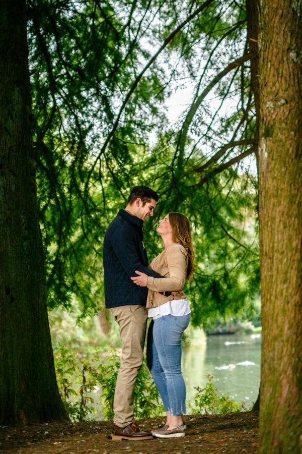 Das Paar schaut sich verliebt in die Augen, umgeben von einem Dach aus Tannengrün.