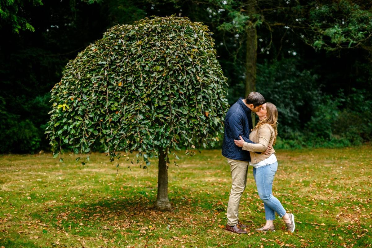 Bei einem Engagementshooting treffen wir uns vor der Hochzeit mit dem Paar und machen natürliche Bilder. Hier küssen sich die Beiden neben einem Baum.