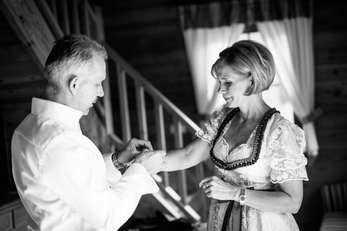 Der Bräutigam hilft seiner Braut den Schmuck anzulegen...