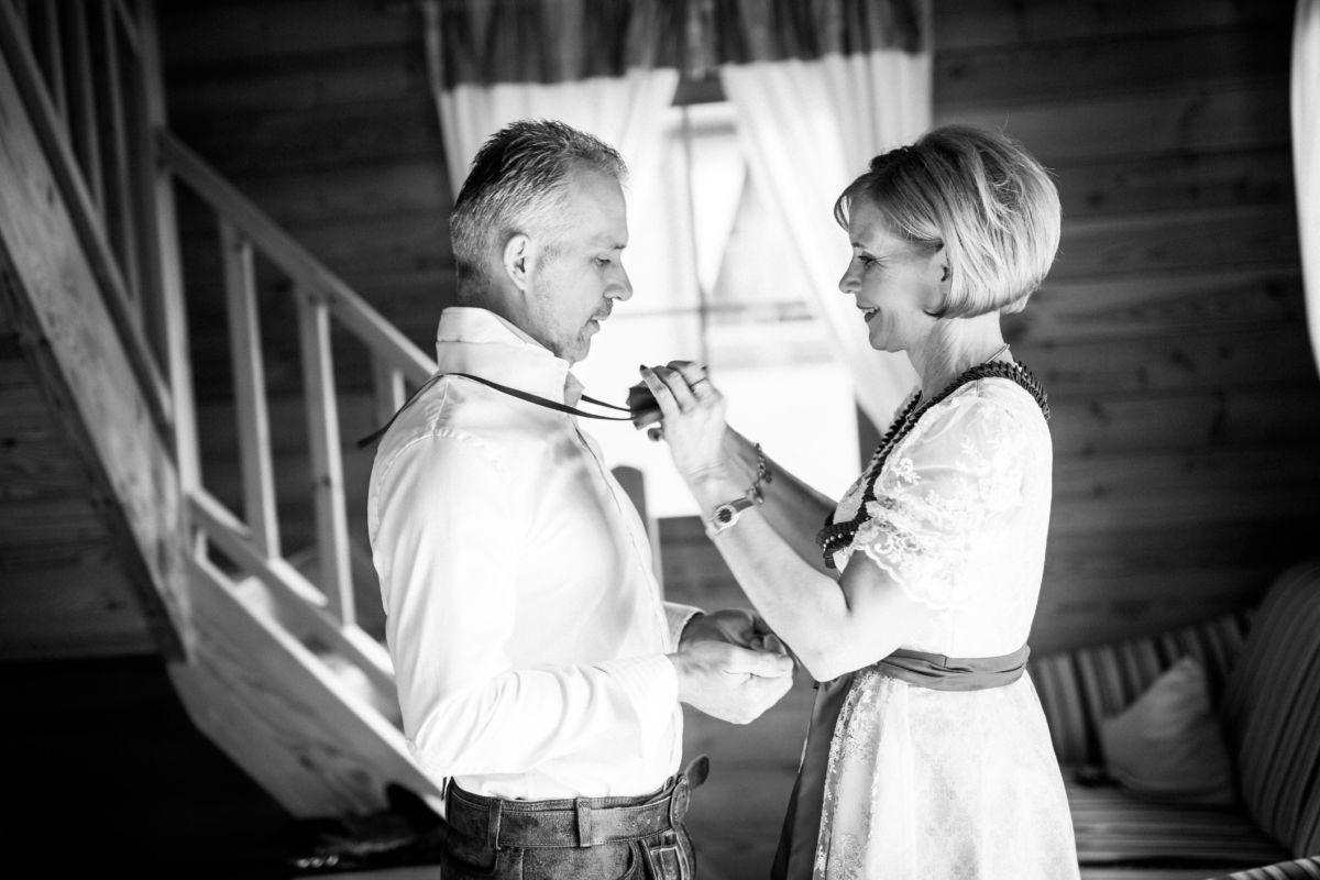 Die Brat hilft ihrem Bräutigam beim Ankleiden