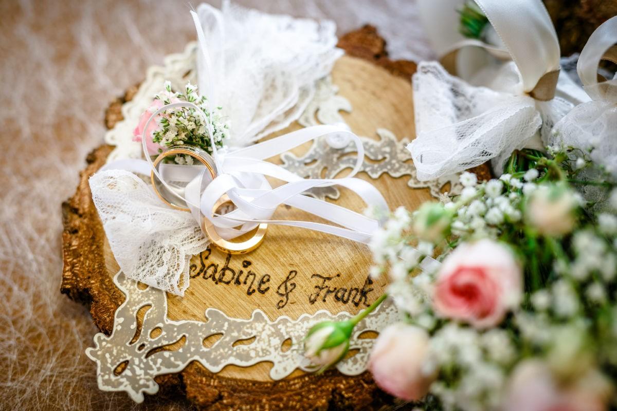 Die Eheringe sind für die Trauung auf einer rustikalen Baumscheibe drapiert
