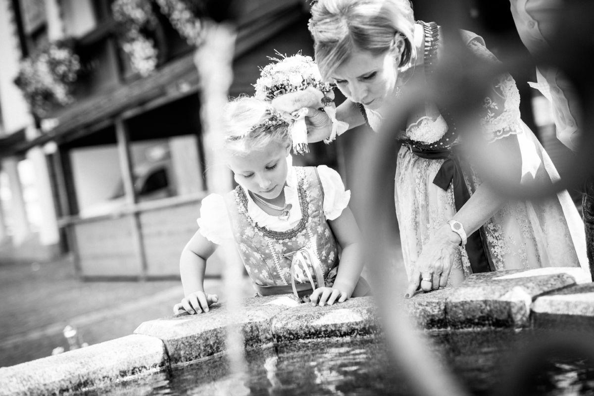 Das Brautpaar wirft eine Münze in den Wunschbrunnen