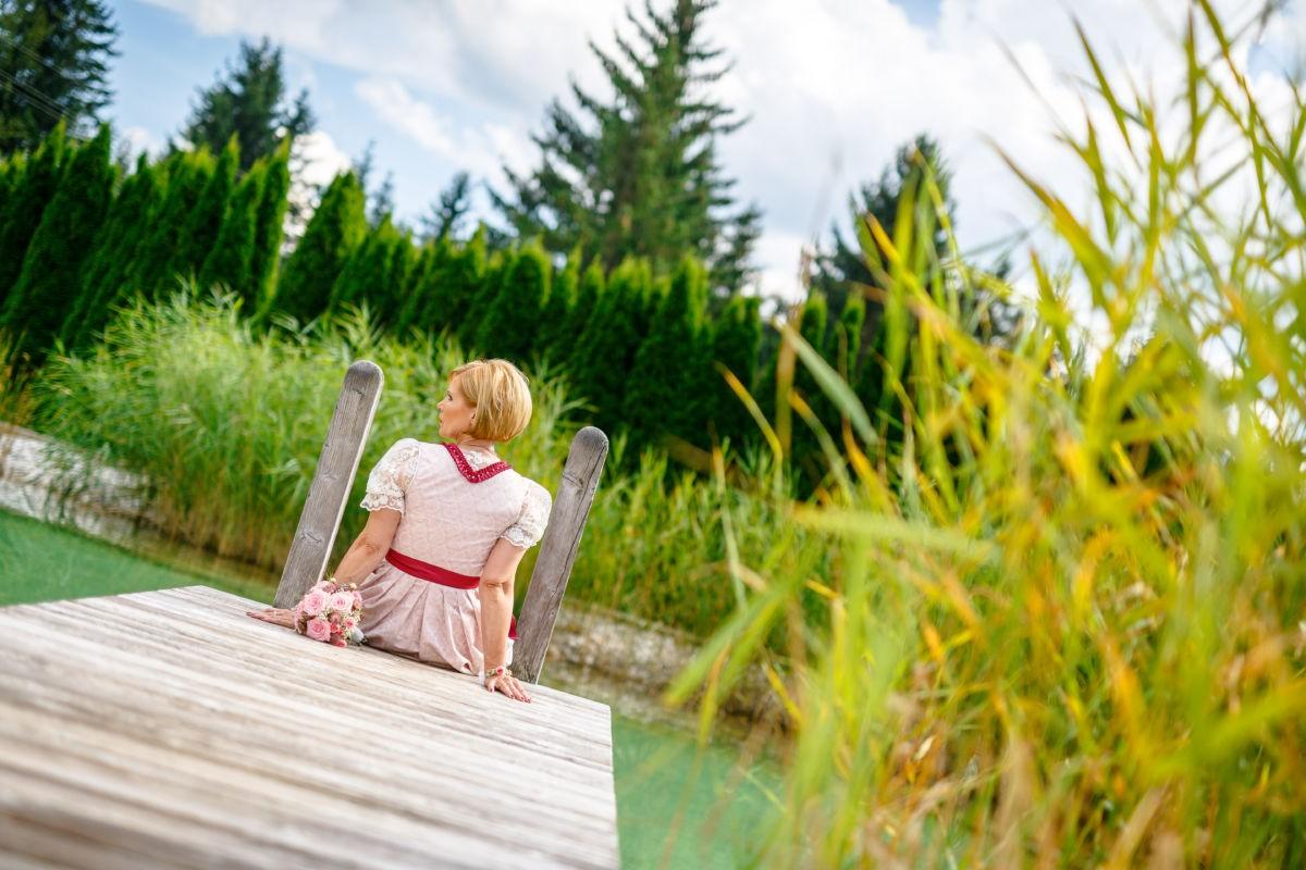 Die Braut sitzt in Tracht auf einem Steg der in einen See führt