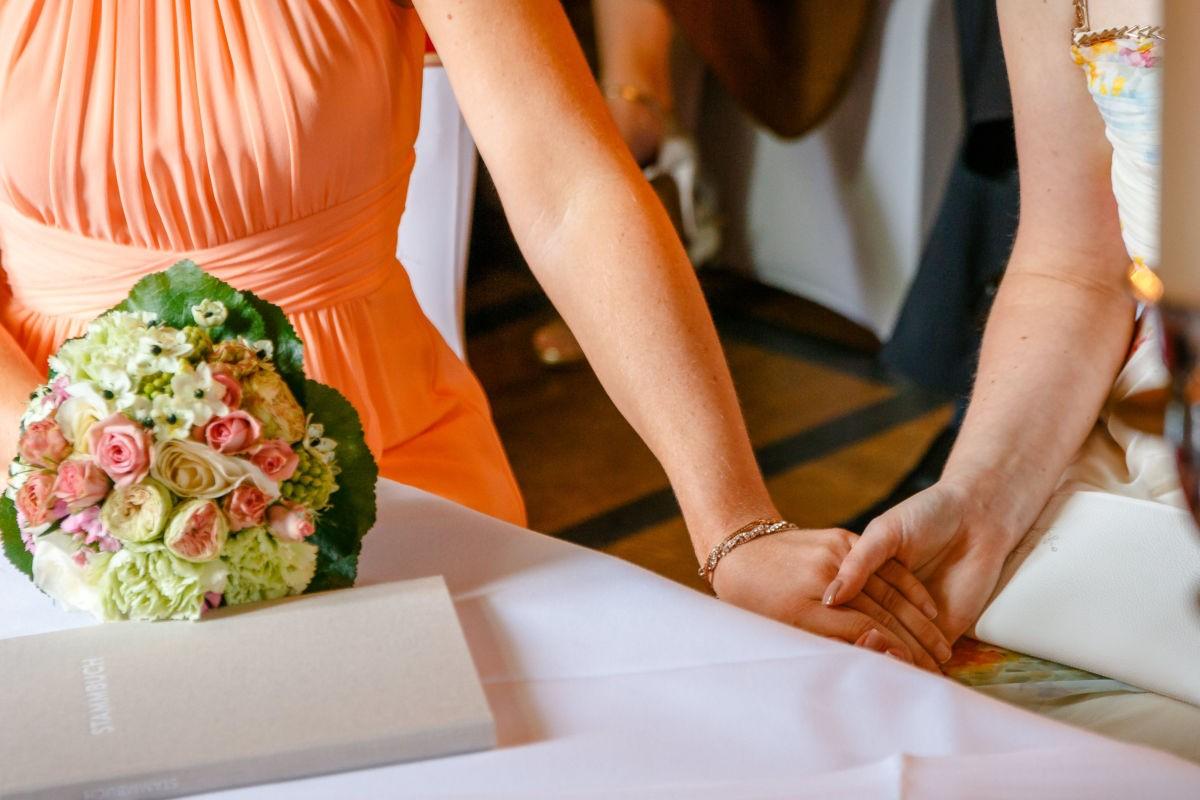 Die Trauzeugin hält während der Trauung in der Marienburg in Langenfeld die Hand der Braut