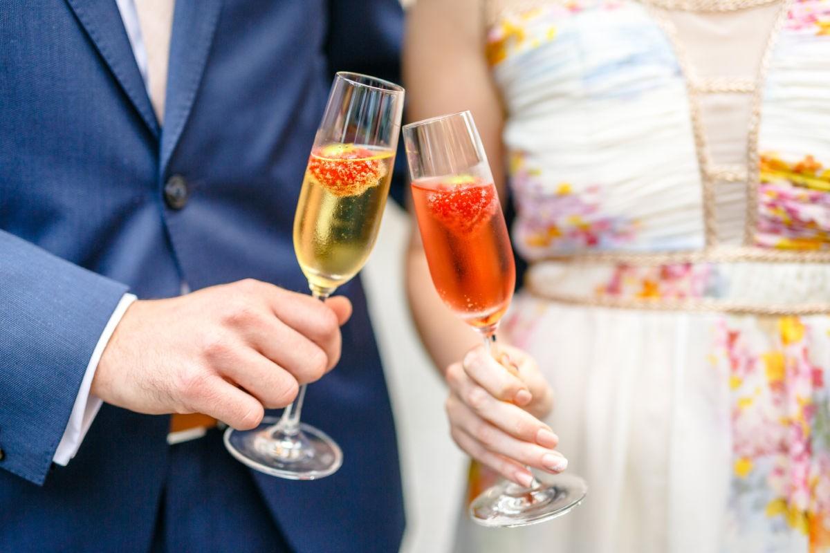 Das Brautpaar stößt mit zwei Sektgläsern an.