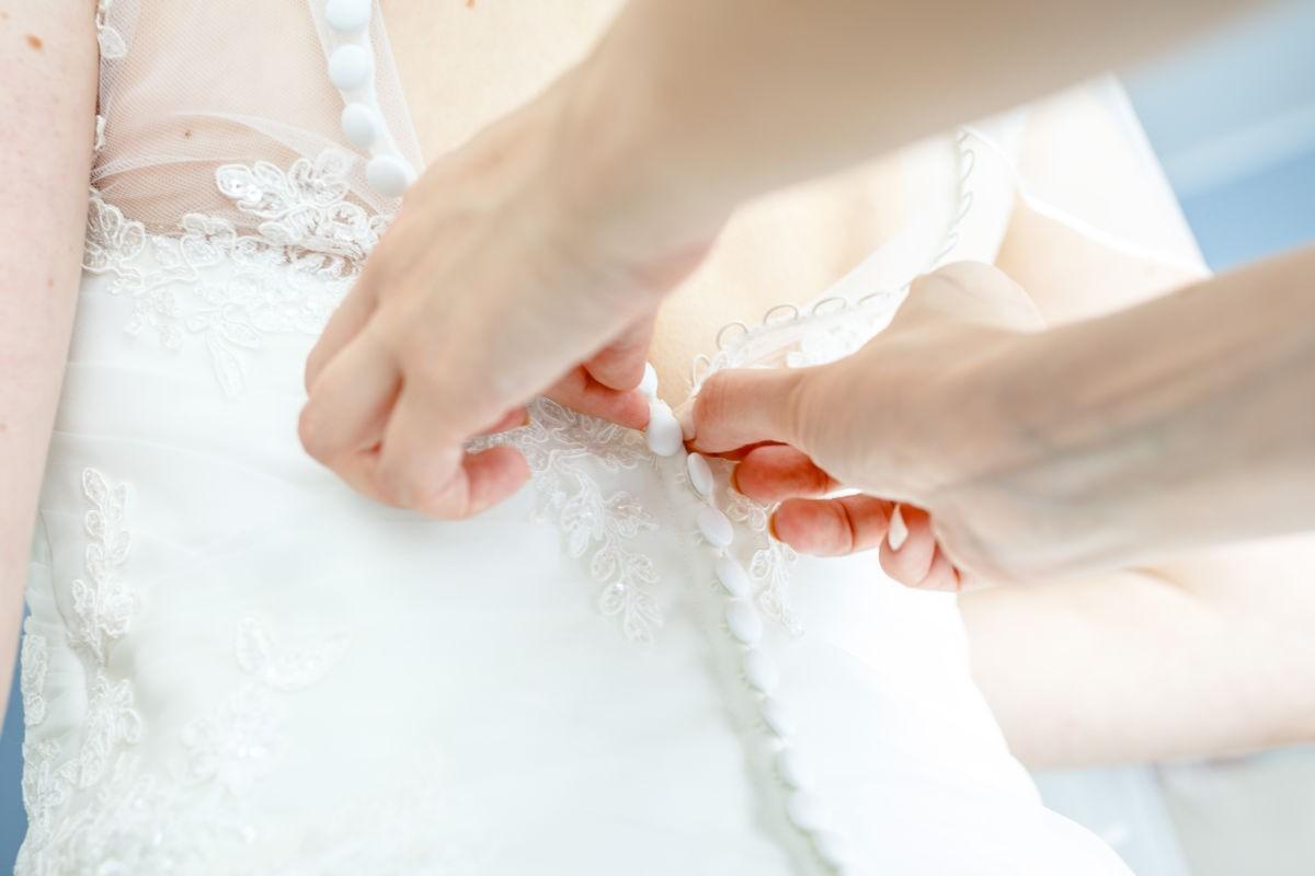 die Trauzeugin knöpft der Braut das lange Kleid zu; solche Aufnahmen entstehen beim Getting Ready der Braut