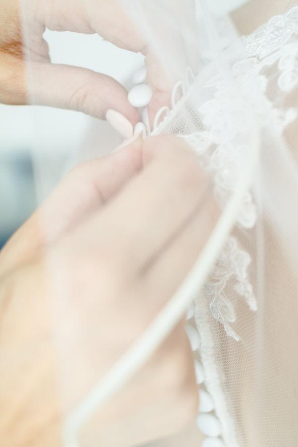 Die knopfleiste des Brautkleides schimmert durch den Schleier hindurch