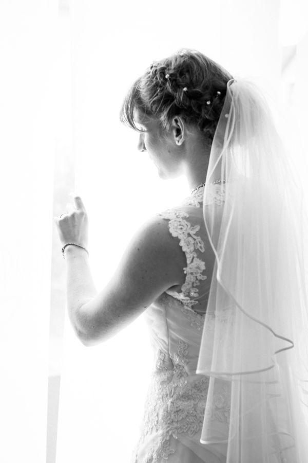 Beim Getting Ready schaut die Braut aus dem Fenster ihrer glücklichen Zukunft entgegen