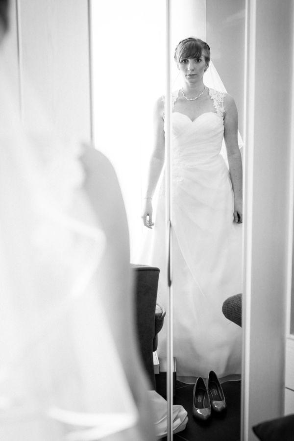 Die Braut sieht sich aufgeregt im Spiegel an bei ihrem Getting Ready in Langenfeld