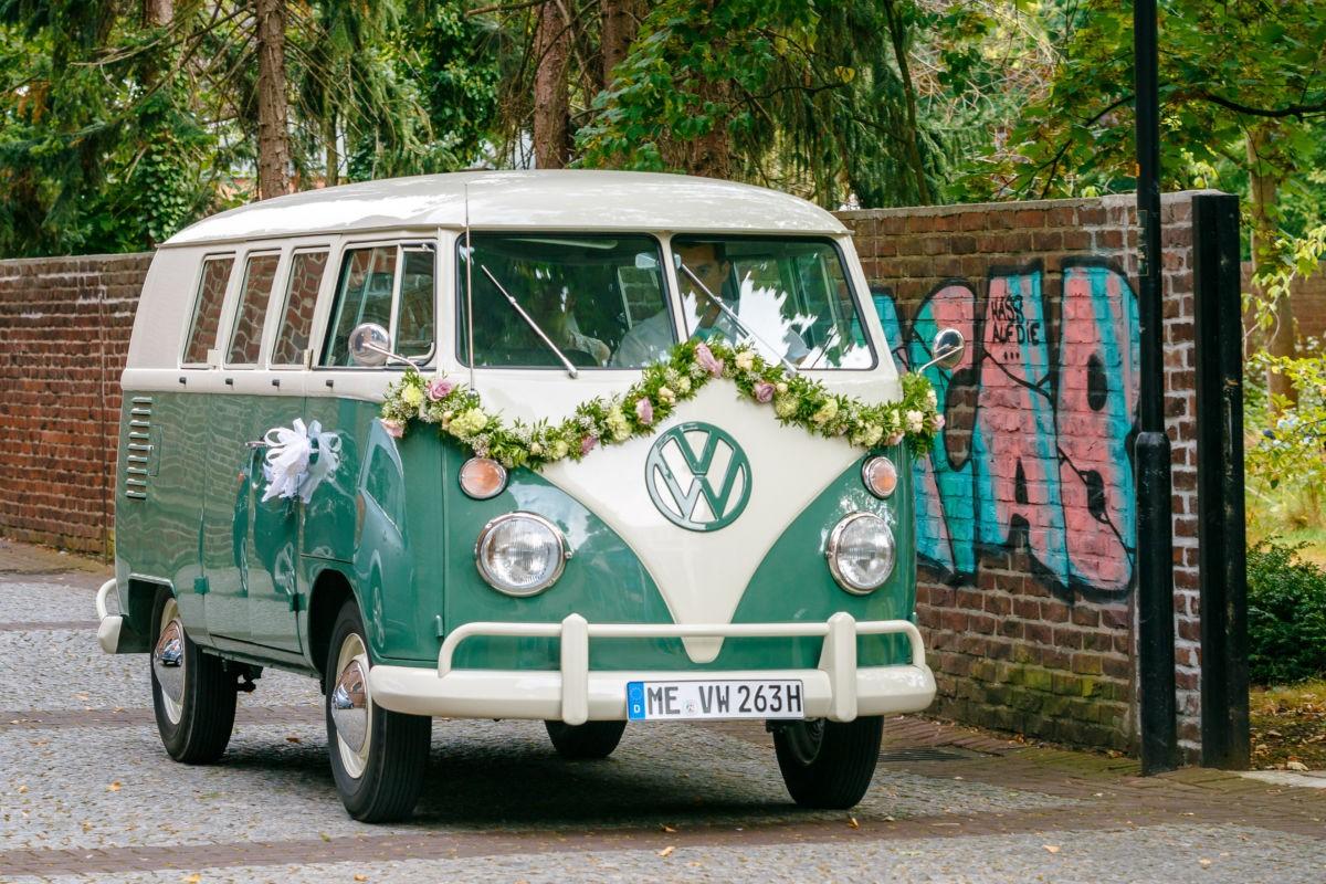 ein alter VW Bulli wird schön geschmückt zum Brautauto und ist ein Hingucker auf den Hochzeitsfotos in Langenfeld