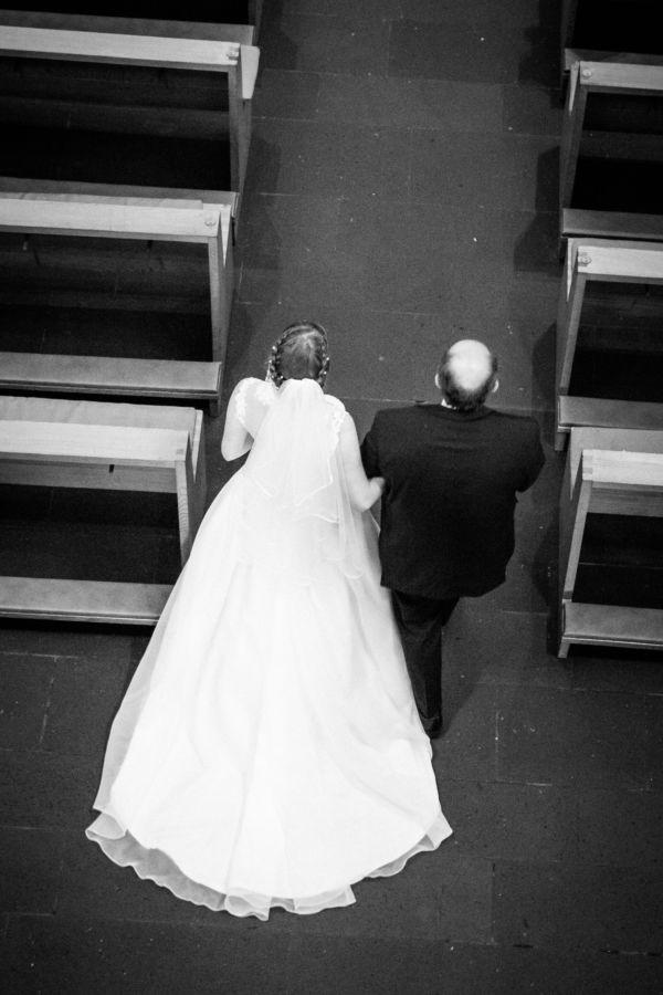 Am Arm des Brautvaters wird die Braut in die Kirche geführt