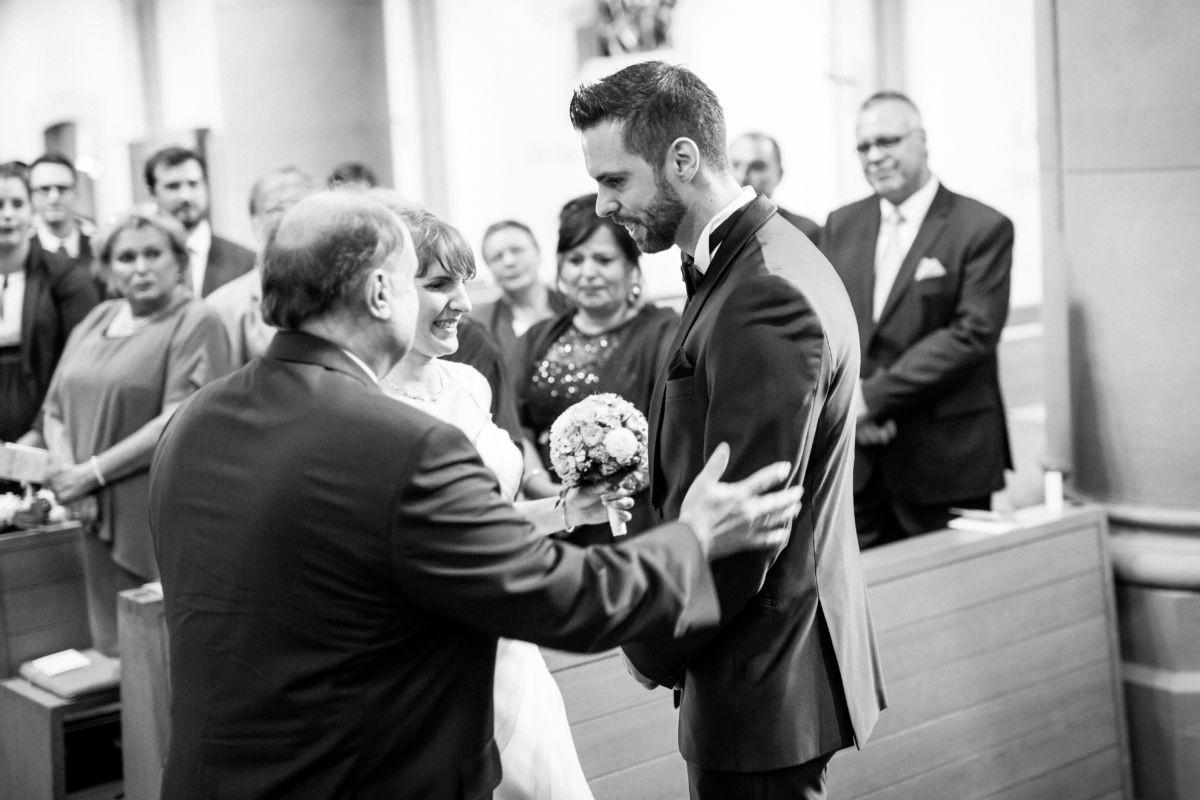 Der Vater der Braut legt die Hände seiner Tochter in die des Bräutigams