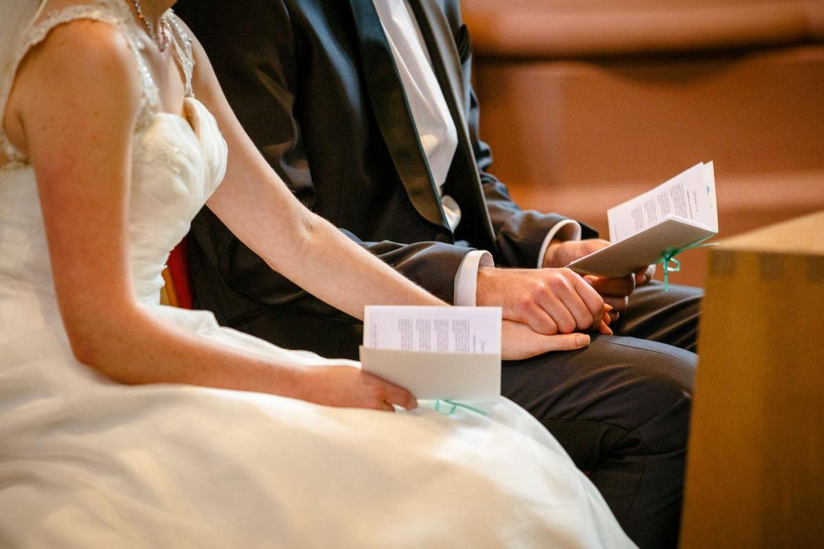 Nhaufnahme der Hände des aufgeregten Brautpaares in der Kirche