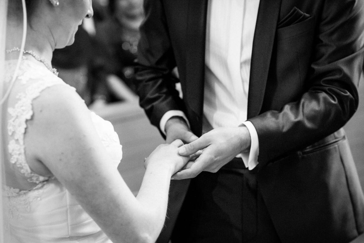In Nahaufnahme steckt der Bräutigam seiner Braut den Ehering an den Finger