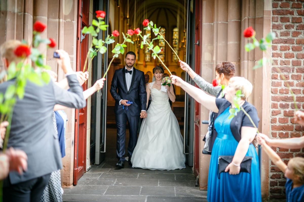 Vor der Kirche warten alle Gäste auf das frischverheiratete Paar und begrüßen es mit Blumen und Seifenblasen