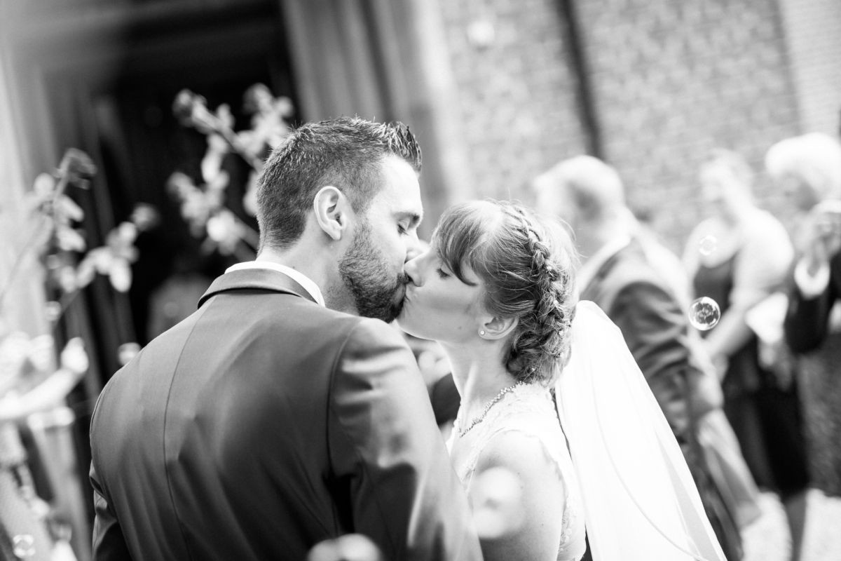 das verliebte Brautpaar küsst sich vor der Kirche in Langenfeld