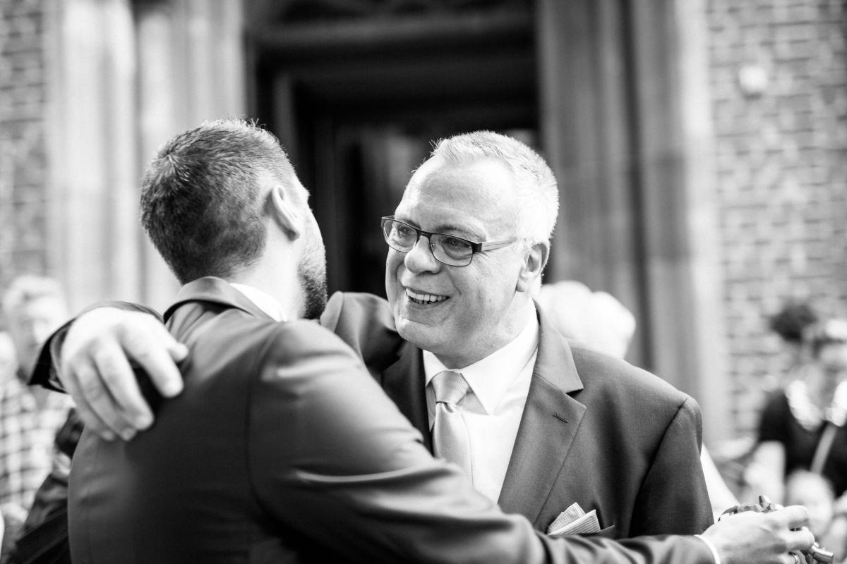 Der Vater umarmt seinen Sohn bei der Hochzeit in Lagenfeld