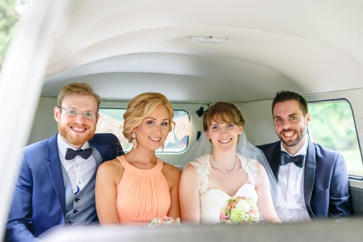 das Brautpaar zusammen mit den Trauzeugen im Brautauto