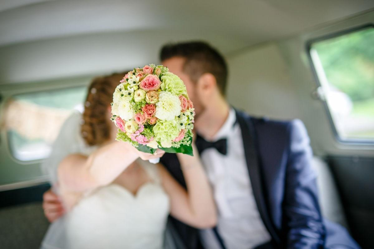 Das Brautpaar küsst sich im VW Bulli nach der Hochzeit