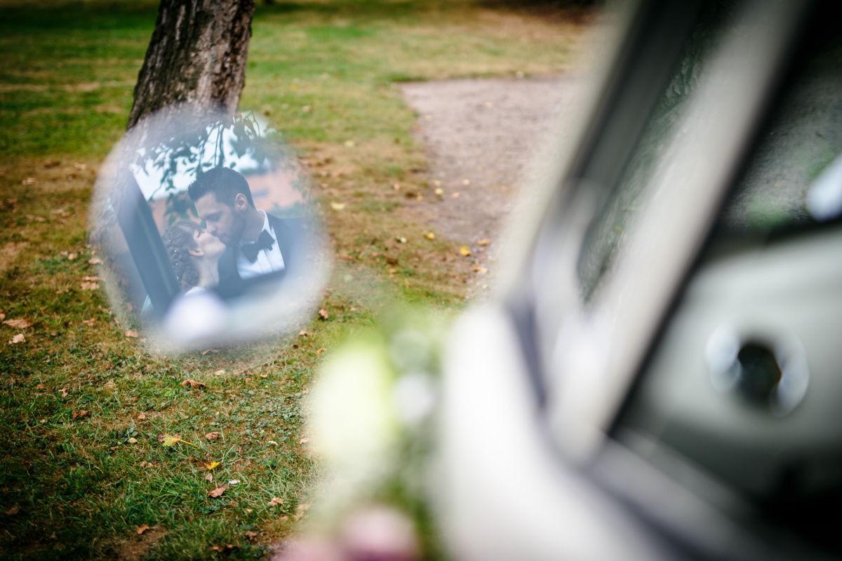 Das küssende Brautpaar spiegelt sich im Seitenspiegel des VW Bullis