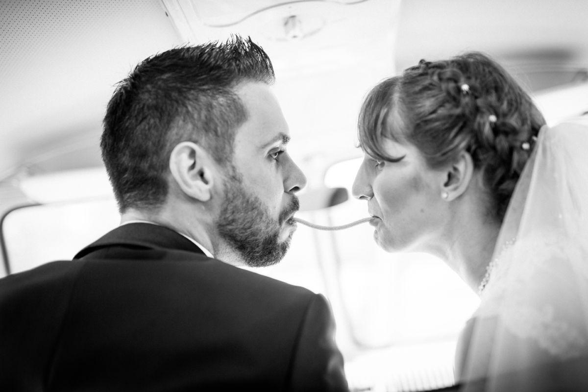 Das Brautpaar isst gemeinsam eine Gummischnur im alten VW Bulli
