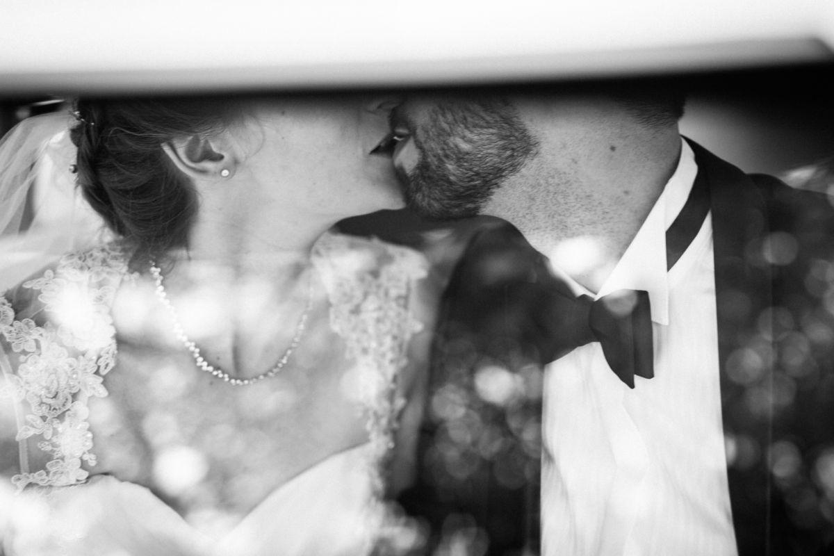 Hochzeitsbild: Das Brautpaar küsst sich im Auto