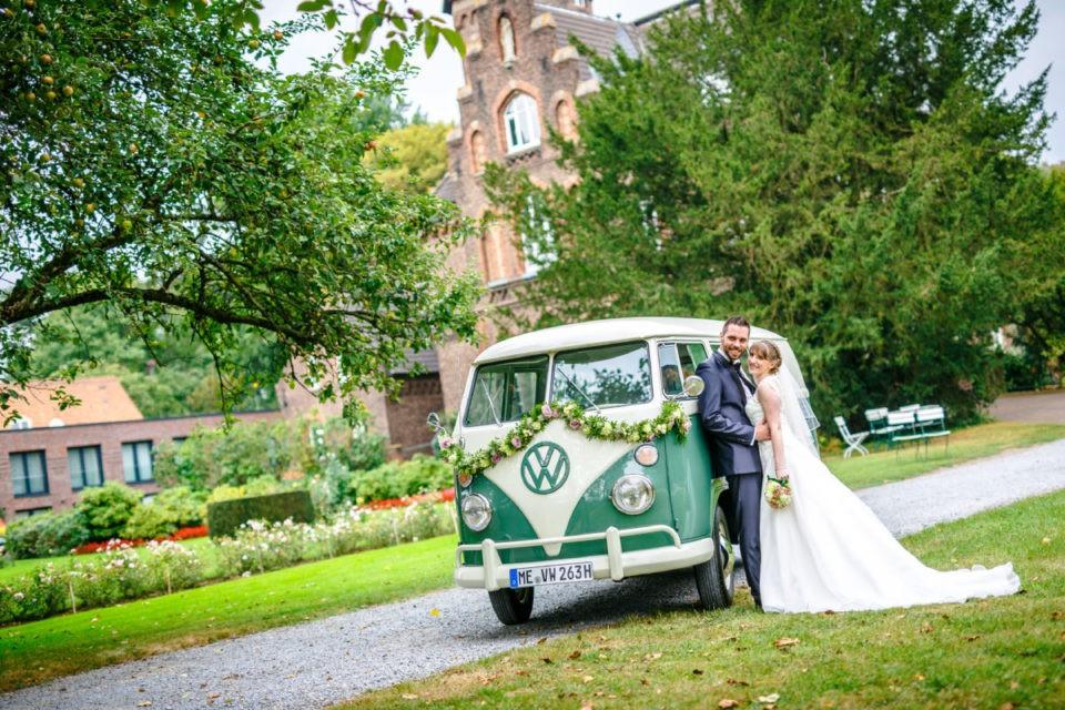 Ein alter VW Bulli dient zusammen mit der Marienburg in Langenfeld als ideales Accessoire auf Hochzeitsbildern