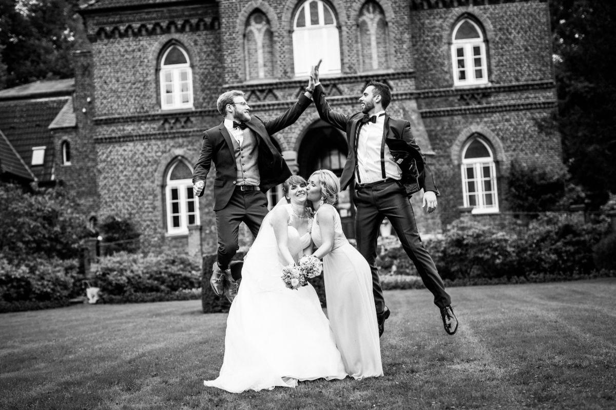 Bräutigam und Trauzeuge geben sich über der Braut und deren Trauzeugin five