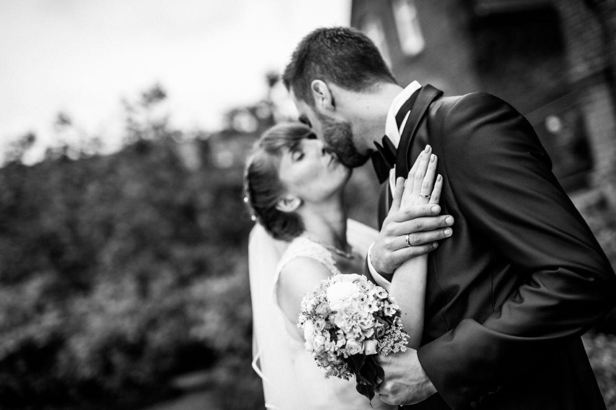 Fokus liegt auf den verschlungenen Händen des Brautpaares, unscharf im Hintergrund küssen sie sich