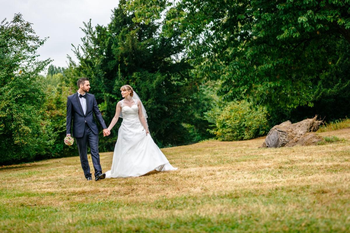 Das Brautpaar spaziert und sieht sich dabei verliebt an