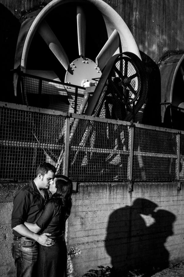 Das Paarshooting in Dusiburg zeigt ein küssendes Paar, dessen Schatten sich auf einer Industriemauer abzeichnet