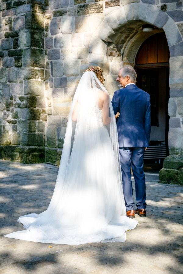 Kurz vor dem Einzug in die Kirche sind Braut und Brautvater von hinten zu sehen