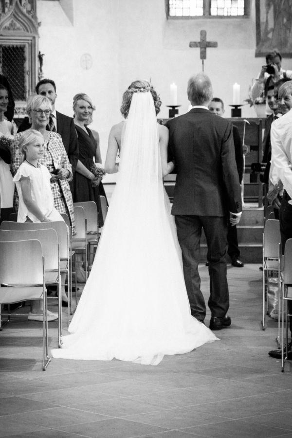 Braut und Brautvater sind von hinten auf dem Weg zum Altar zu sehen