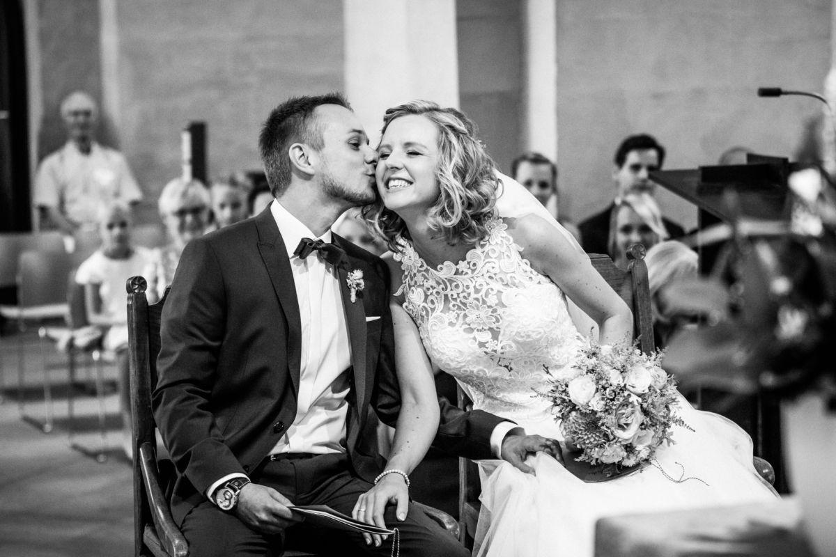 Der Bräutigam küsst seine Braut in der Kirche auf die Wange