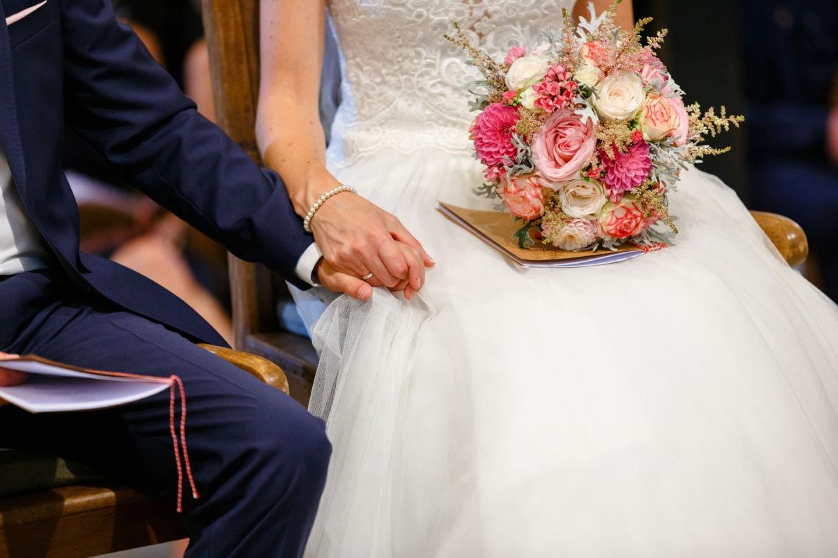 Die Hände des Brautpaares sind zusammen mit dem Brautstrauß im Fokus.