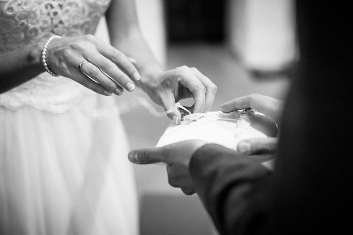 Die Braut nimmt den Ehering vom Kissen