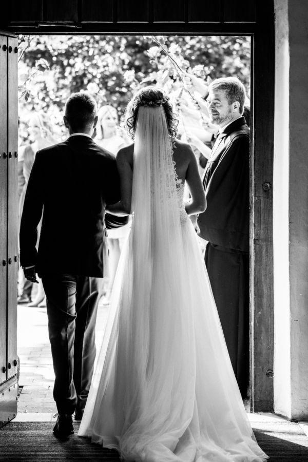 Das Brautpaar ist von hinten zu sehen wie es die Kirche verlässt
